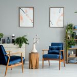 Posters and plants in bright living room interior with navy blue